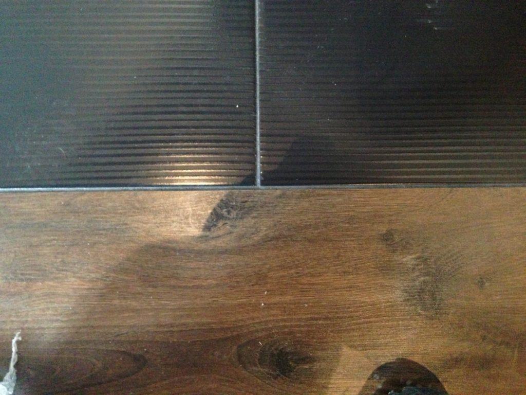 Стык плитки и ламината пеной и герметиком